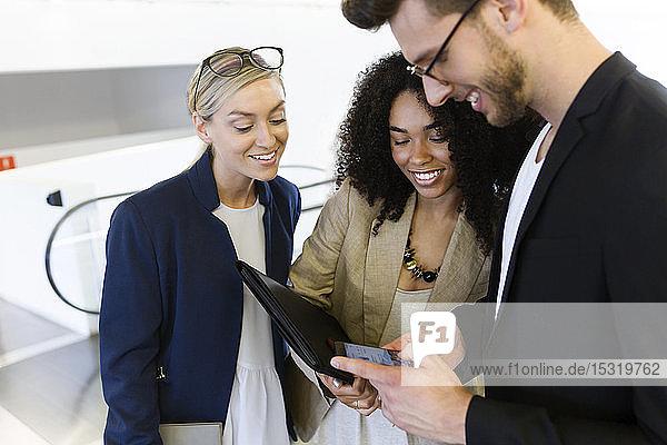 Drei junge Geschäftsleute teilen sich ein Smartphone