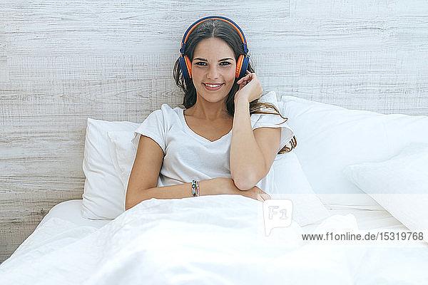Porträt einer lächelnden jungen Frau,  die mit Kopfhörern im Bett liegt