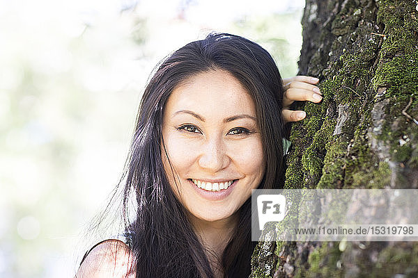 Portrait of a young smiling woman leaning at a tree trunk