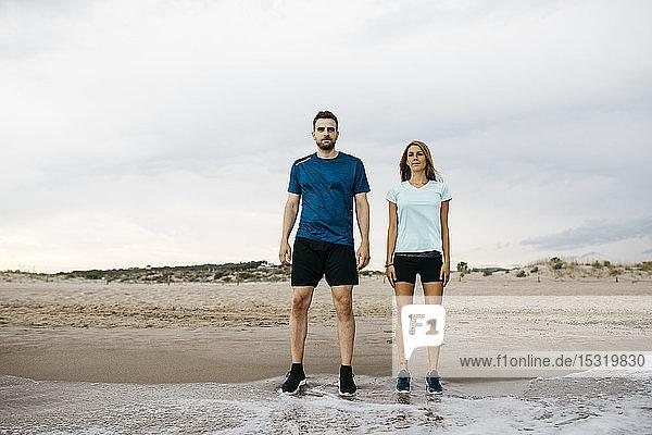 Junge Jogger stehen am Strand