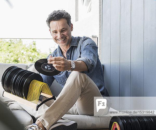 Mature man sitting at home  looking at vintage sigle recors