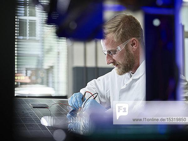 Techniker misst den Kontakt einer Silizium-Solarzelle auf einem Solarpanel