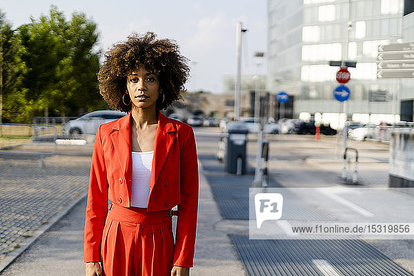 Porträt einer jungen Frau in einem modischen roten Hosenanzug