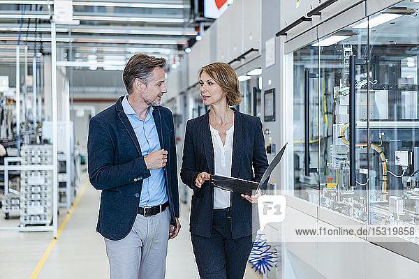 Geschäftsmann und Geschäftsfrau im Gespräch in einer modernen Fabrikhalle