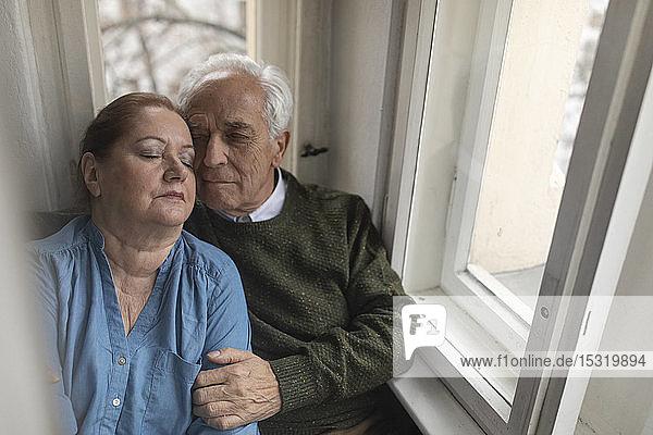 Porträt eines liebevollen älteren Ehepaares am Fenster