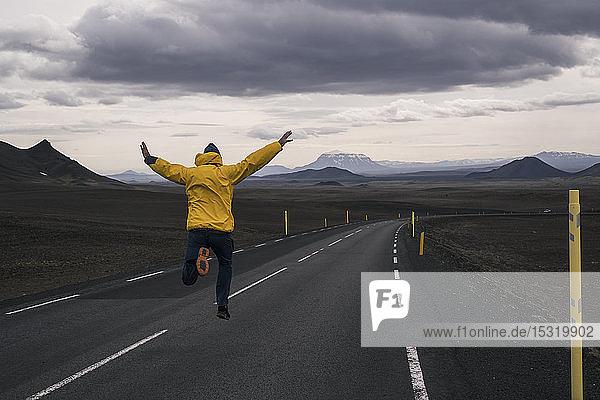 Glücklicher Mann springt vor Freude auf einer leeren Straße  Island