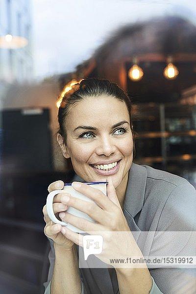 Porträt einer Geschäftsfrau hinter einer Fensterscheibe in einem Café beim Kaffeetrinken