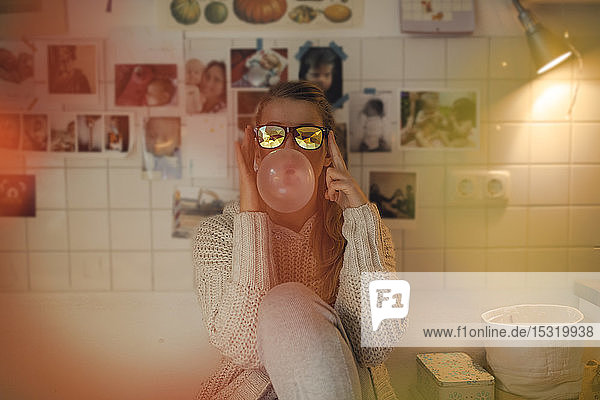 Young woman at home wearing sunglasses making chewing gum bubble