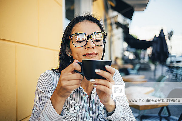Young woman enjoying a cup of coffee in a cafe