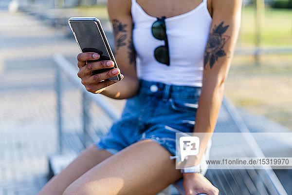 Hand einer tätowierten jungen Frau  die ein Smartphone hält  Nahaufnahme