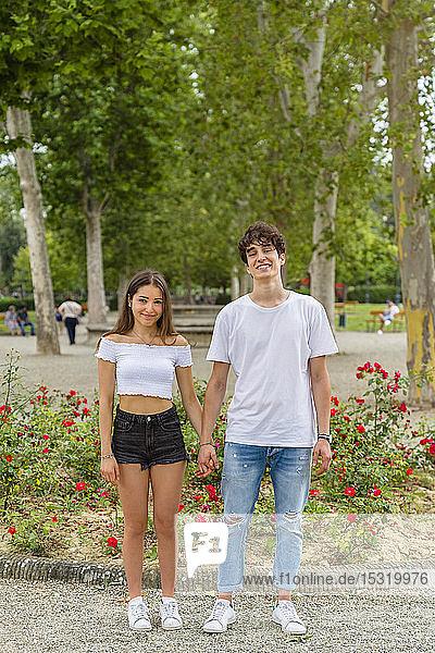 Junges Paar hält Händchen in einem Park
