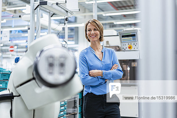 Portrait of businesswoman at assembly robot in a factory