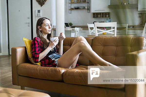 Entspannte junge Frau isst zu Hause im Wohnzimmer Müsli