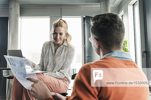 Businessman and woman with laptop meeting in office