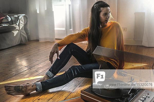 Junge Frau  die zu Hause mit einem Plattenspieler auf dem Boden sitzt