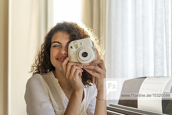 Lächelnde junge Frau zu Hause am Klavier beim Fotografieren
