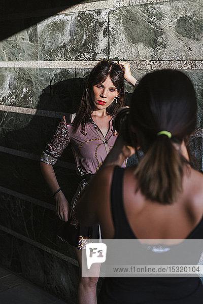 Junge Frau in gemustertem Kleid posiert für ein Fotoshooting