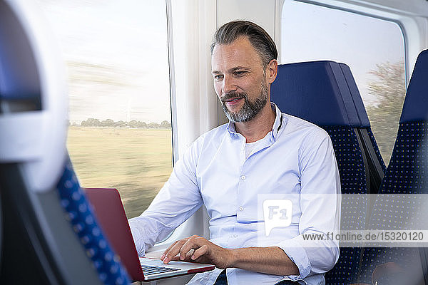 Mature man sitting in a train  using laptop