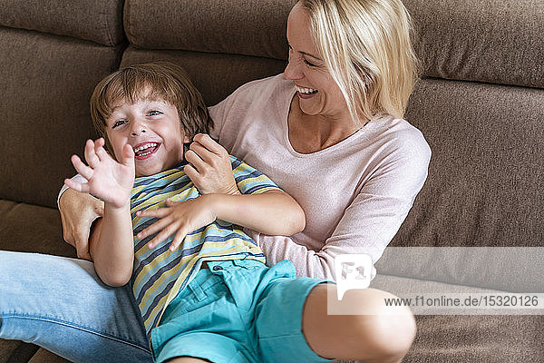 Playful mother and son on couch at home