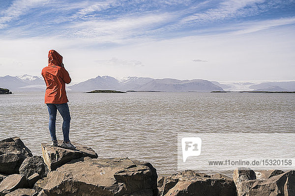 Junge Frau steht auf Felsblöcken und schaut auf das Meer  Südost-Island
