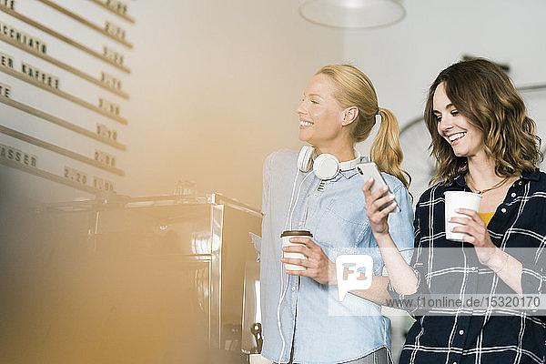 Zwei junge Frauen stehen stolz in ihrem eigenen Café