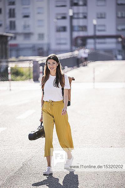 Junge Frau mit Geigenkoffer auf der Strasse