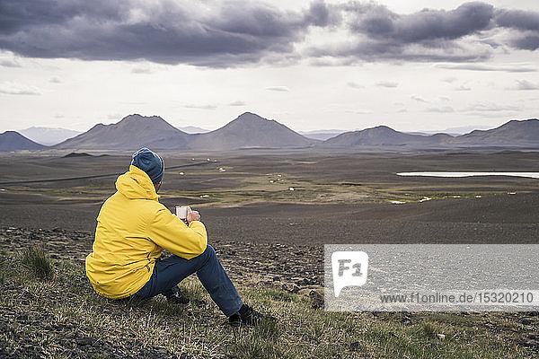 Mann beim Kaffeetrinken  Blick auf Landschaft in Island