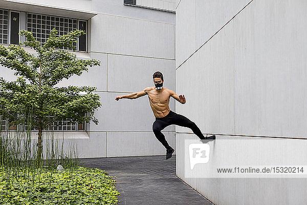 Sportler beim intensiven Training mit Atemmaske  Sprung gegen Hauswand