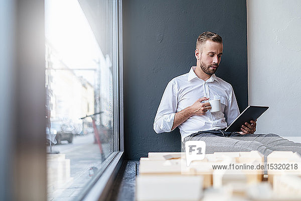 Businessman with tablet  cup of coffee and architectural model in office