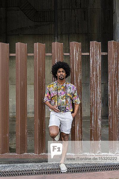Mann mit Kamera  der ein buntes Hemd trägt und sich gegen einen Zaun lehnt