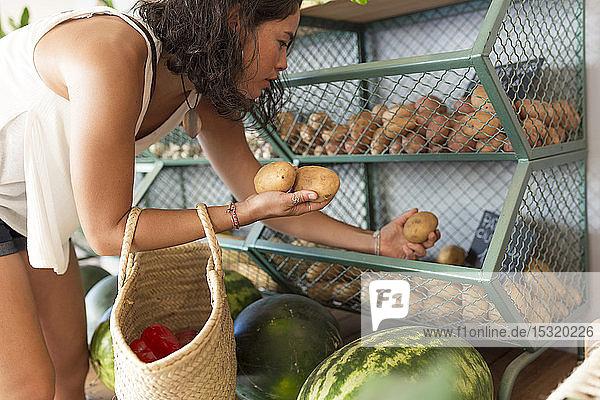 Junge Frau im Bioladen bei der Kartoffelauswahl
