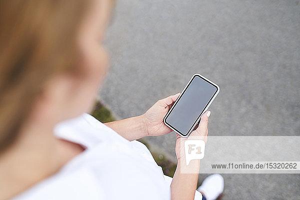 Nahaufnahme einer Frau  die ein Smartphone im Freien benutzt