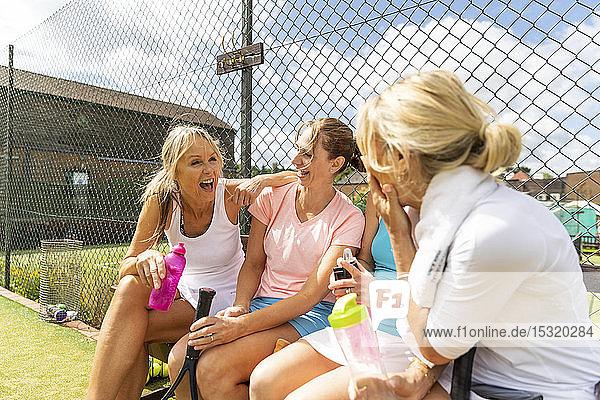 Happy mature women talking at tennis club