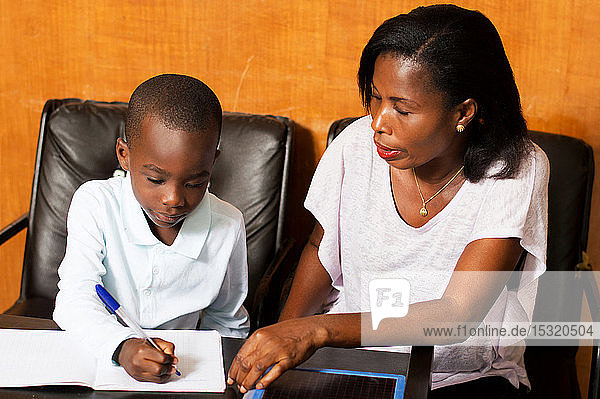 Mom attends child writing in his notebook.