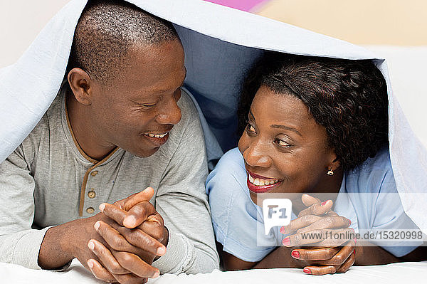 young couple lying under the cover looks  smiling.