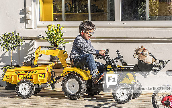 Six-year-old boy driving a toy tractor in the garden