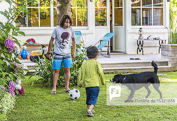 Two boys of 5 years old and 13 years old playing with a ball in the garden with their dog