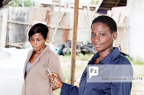 Young woman mechanic holds a key next to the owner of this car.