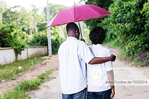 young couples stroll and covered by an umbrella.