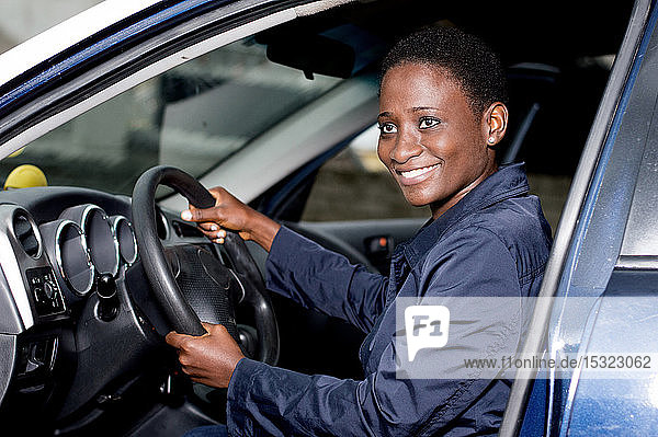 Young woman sitting in a car  hands on the steering wheel smiling at the camera.