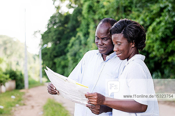 happy young couple in tourism  consult a regional map to find the right road.