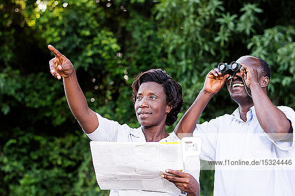 young woman pointing at something the young man looking through binoculars.