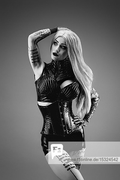 Portrait of a tattooed young woman wearing latex clothes