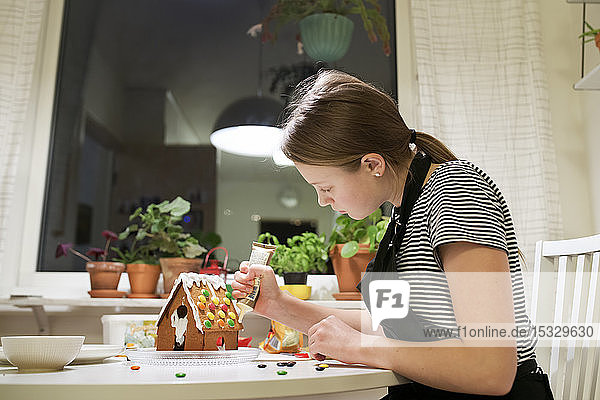 Girl icing gingerbread house