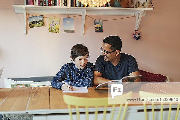 Vater hilft seinem Sohn bei den Hausaufgaben