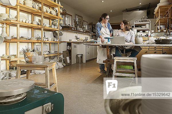Women using laptop in pottery workshop