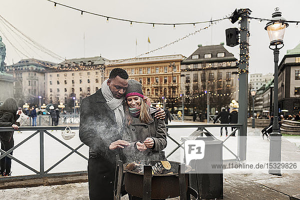 Couple warming their hands over fire