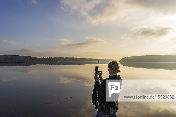 Mid adult woman holding cell phone in front of Lake Aspen in Lerum  Sweden