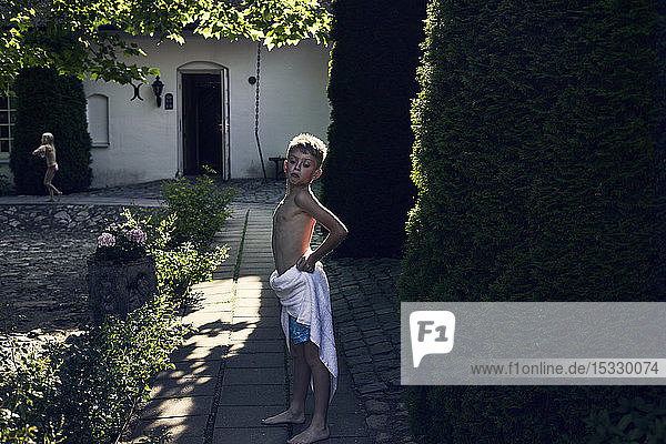 Boy wearing towel in back yard Boy wearing towel in back yard