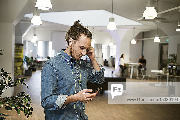 Man using earbuds with smart phone